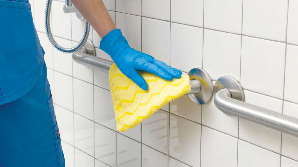 Gloved Hand Wiping Down Grab Bars in Bathroom with Yellow Rag