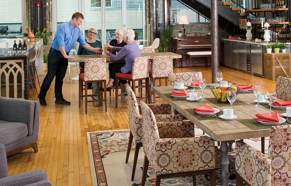 Man Serving Three Elderly Women in Senior Living Dining Room