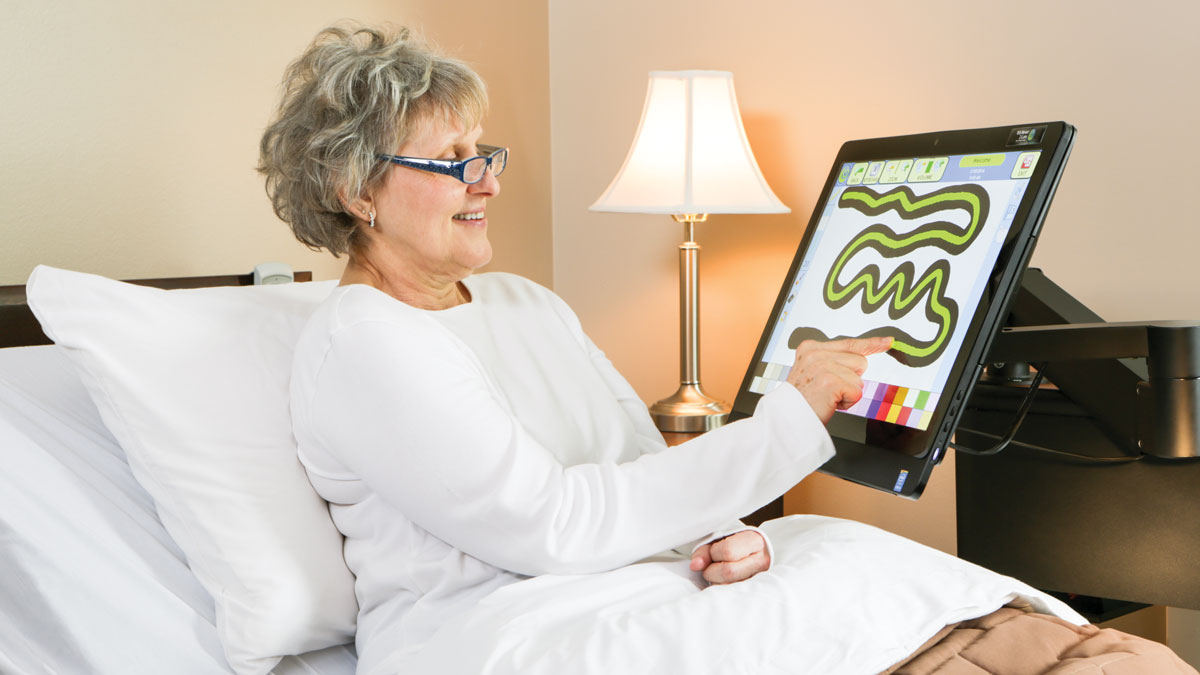 Elderly Woman in Bed Playing Game On Mounted Screen